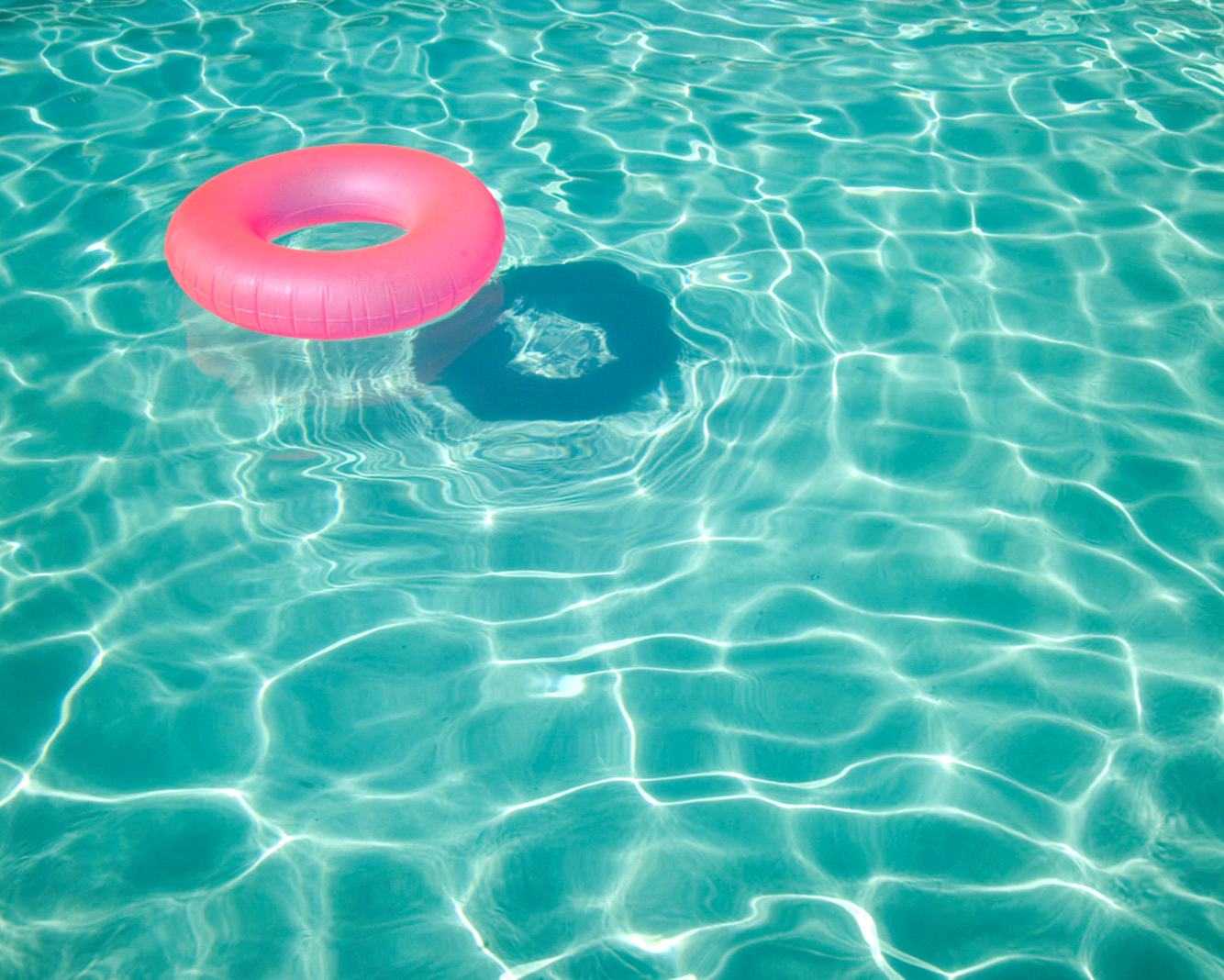 Pink donut floating in pool water