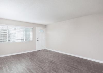 Empty living room with windows and front door